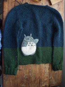 Back of sweater with cheerful big Totoro, waving.
