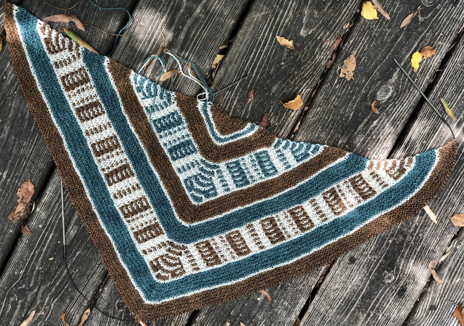 An unfinished striped triangular shawl that uses three colors to make geometric patterns.