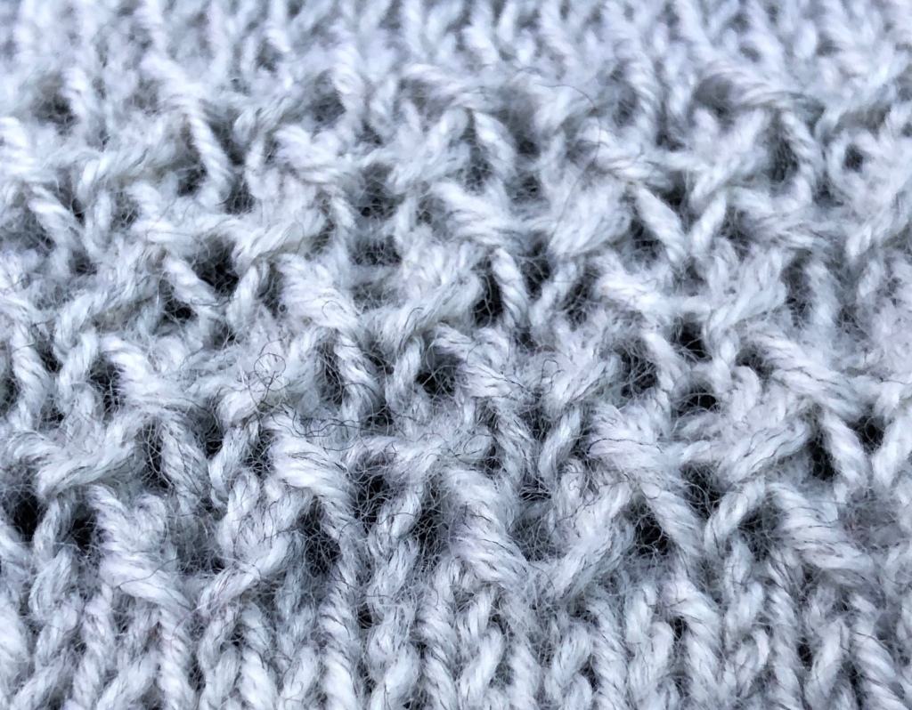 sample knitting for Hyla stitch, showing a thick, open texture and vague impression of flying birds.
