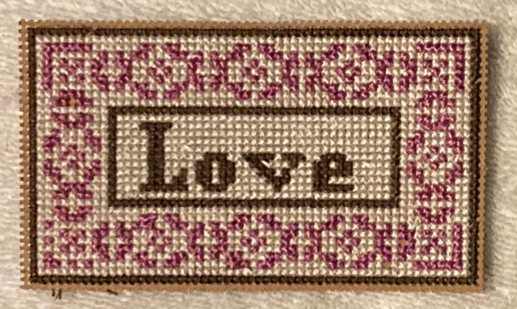 "cross stitched bookmark with the letters ""Love"" in the middle, and the encoded pattern made from Idyll around the edge."